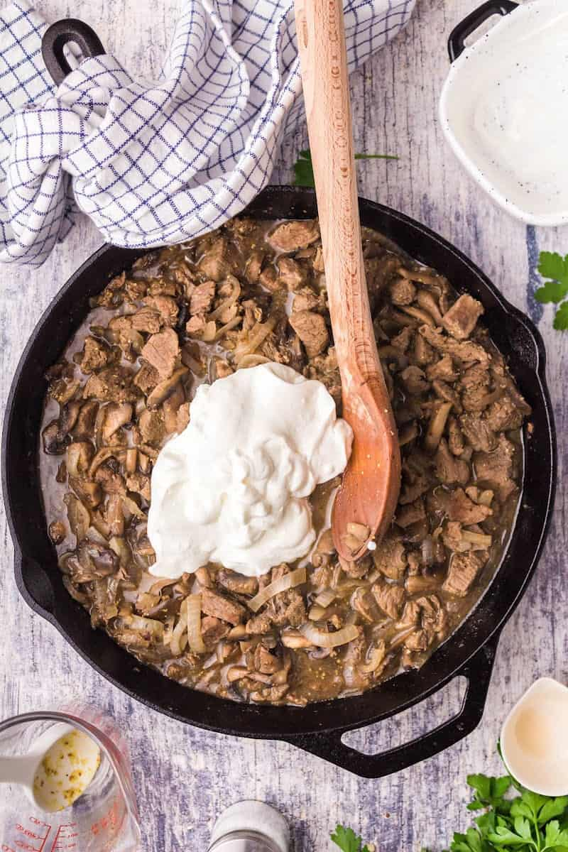 sour cream added to beef gravy, cooked beef, mushrooms, and onions in a skillet
