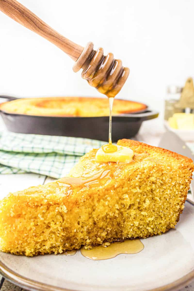 honey being dirzzled on a slice of skillet cornbread with butter