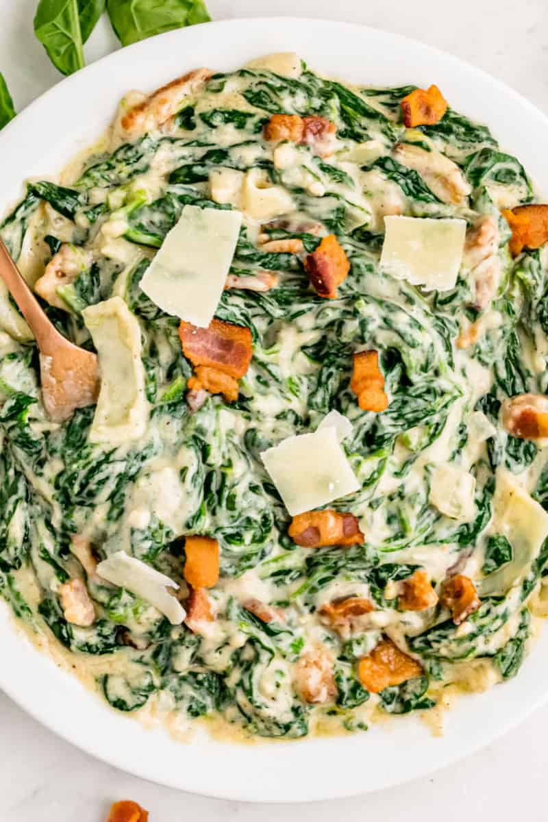 close up of a bowl of creamed spinach topped with bacon and shaved parmesan cheese