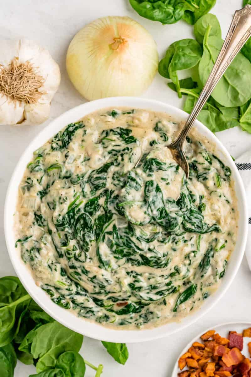 creamed spinach in a serving bowl with a spoon