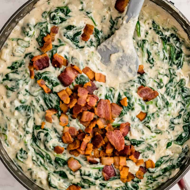 cream spinach stirred togethr in a skillet with cooked bacon on top