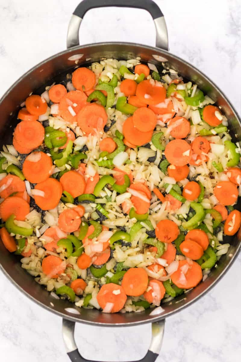 carrots, celery, onion, and garlic being cooked in a large pot
