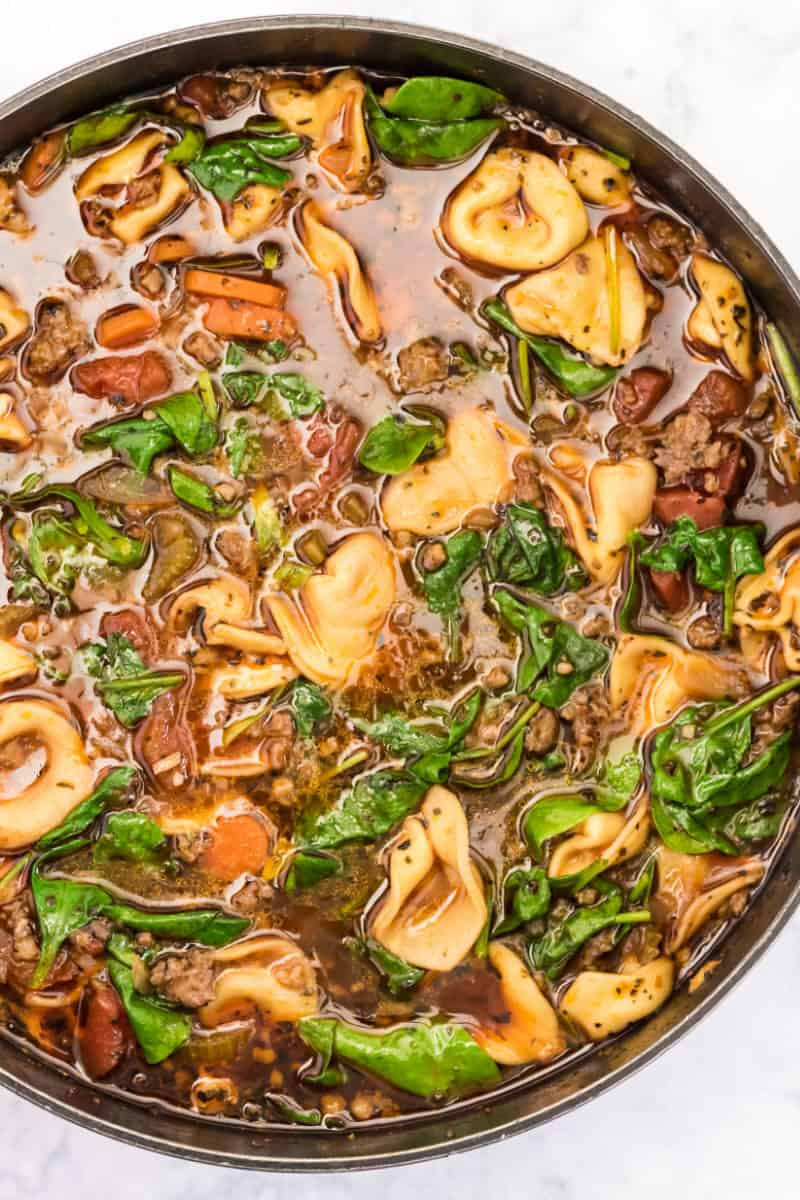 sausage tortellini soup in a pot after simmering