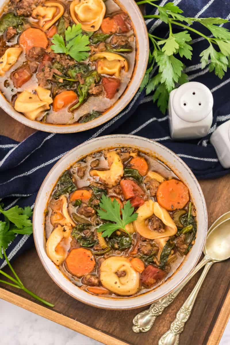bowls of sausage tortellini soup on a wooden tray with spoons