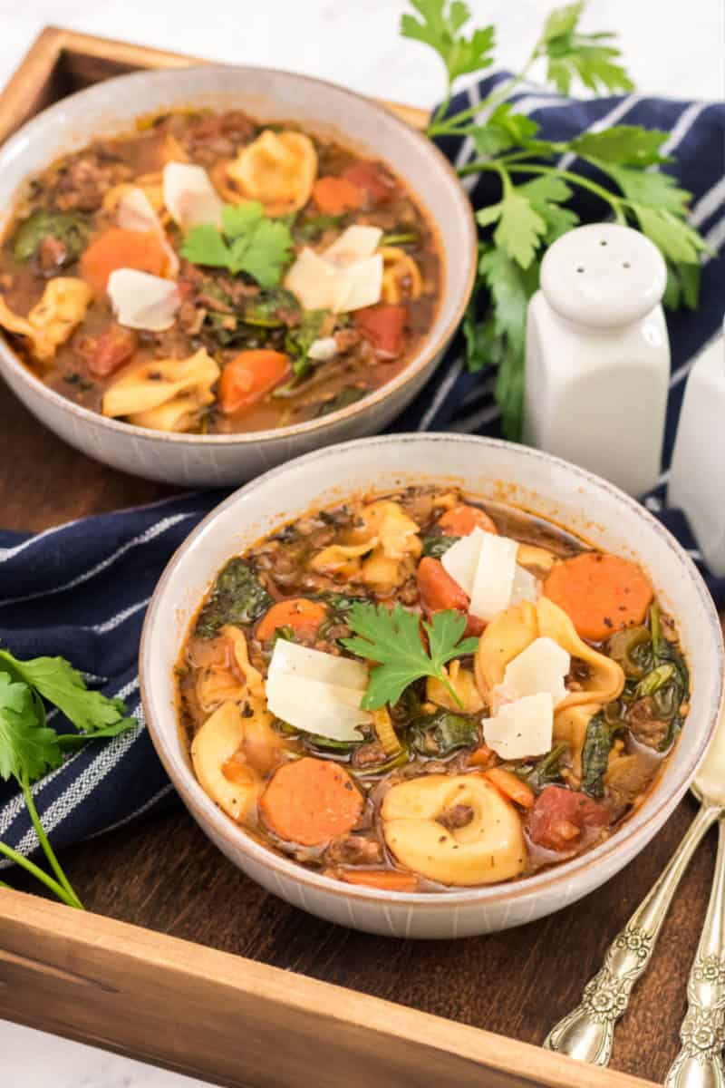 bowls of sausage tortellini soup topped with parmesan and parsley on a wooden tray