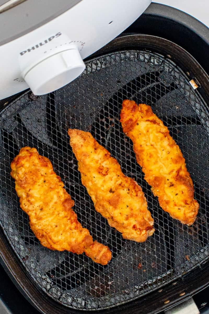 cooked chicken tenders in an air fryer basket