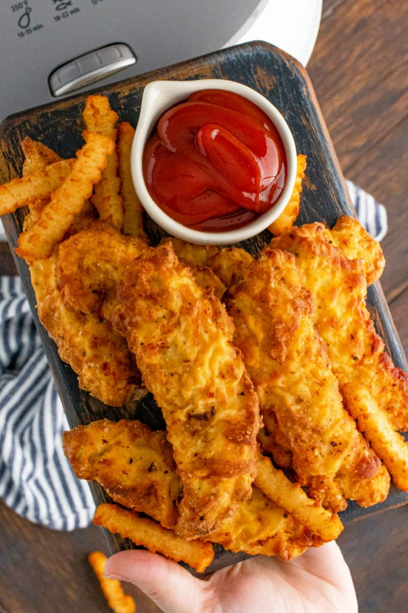 air fryer chicken tenders on a plate with french fries and ketchup