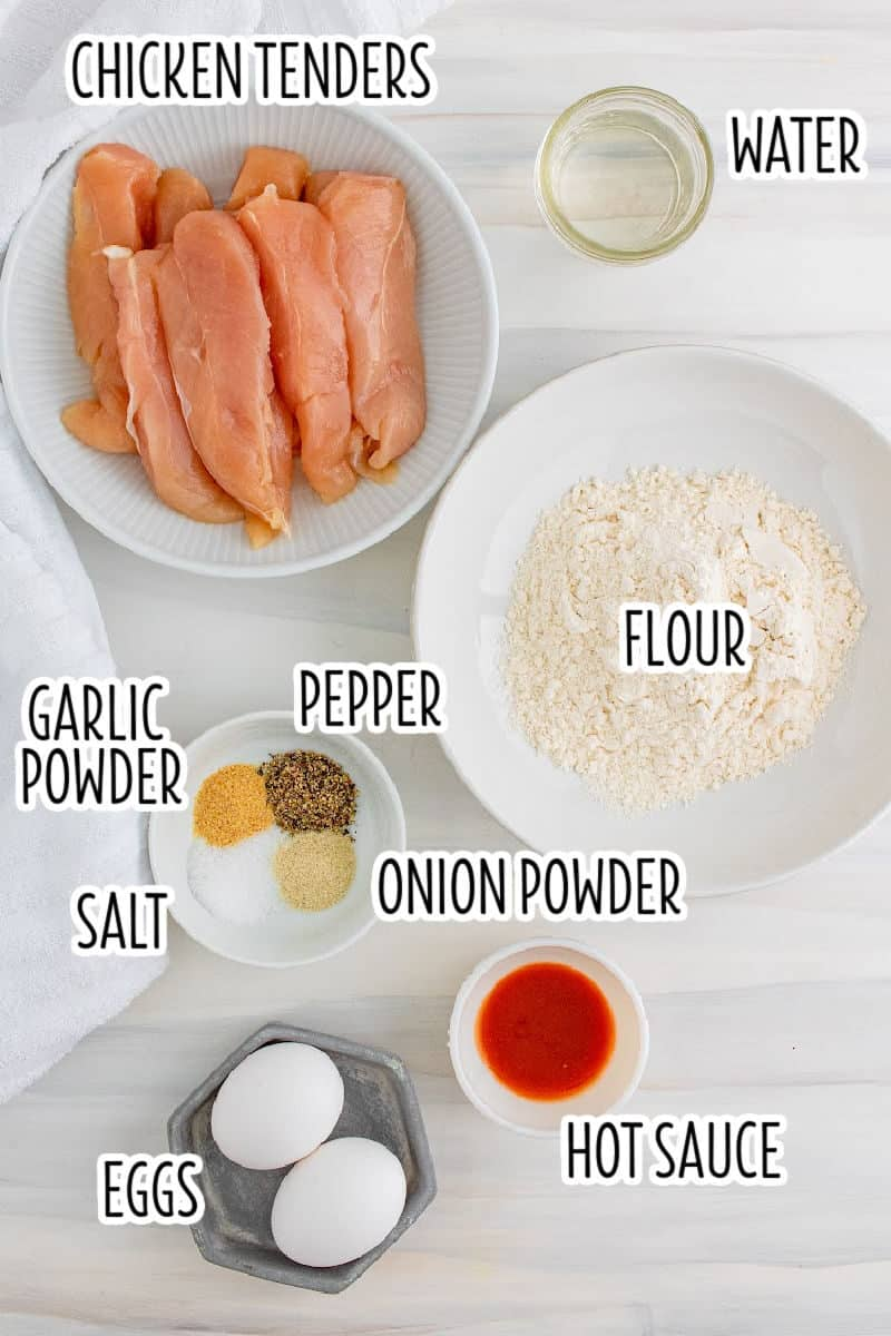 ingredients to make air fryer chicken tenders in bowls on a counter