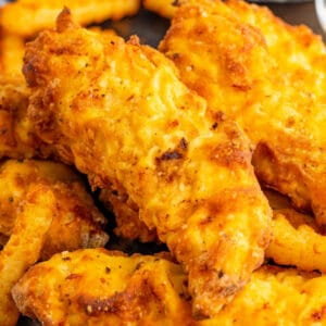 square image of air fryer chicken tenders piled on top of fries