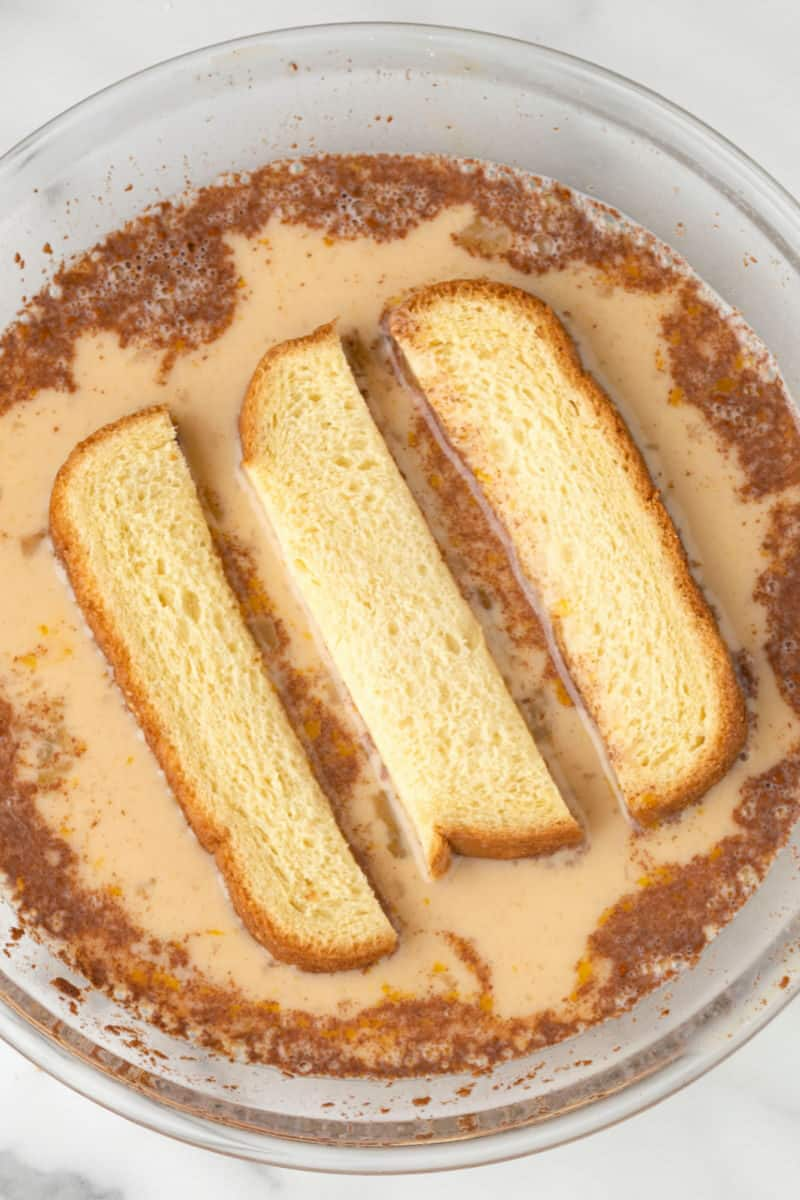 bread sticks being dipped in french toast custard
