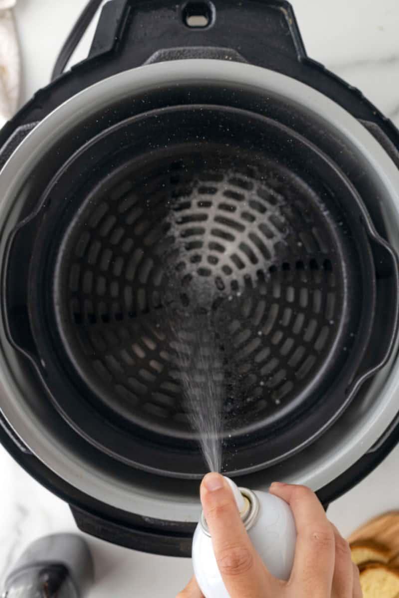 air fryer basket being sprayed with ghee oil spray