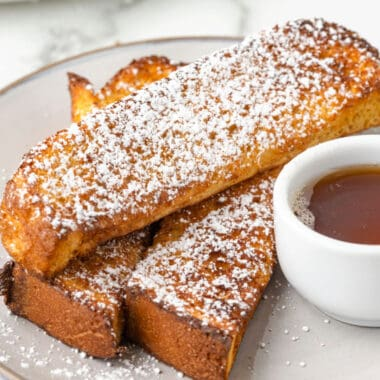 square image of three french toast sticks on a plate next to a cup of syrup