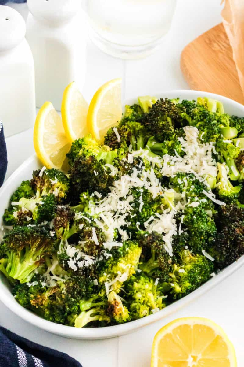 air fryer broccoli with grated parmesan and lemon in a serving bowl next to salt and pepper shakers