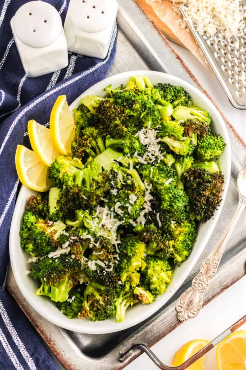 air fryer broccoli with lemon slices and parmesan cheese in a serving bowl on a tray
