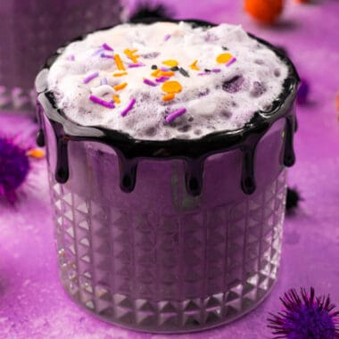 square image of witches brew halloween punch in a glass with black gel icing rim